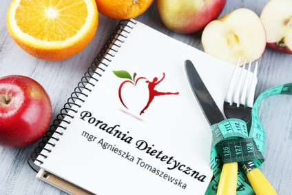 Cutlery tied with measuring tape and notebook with fruits on wooden background